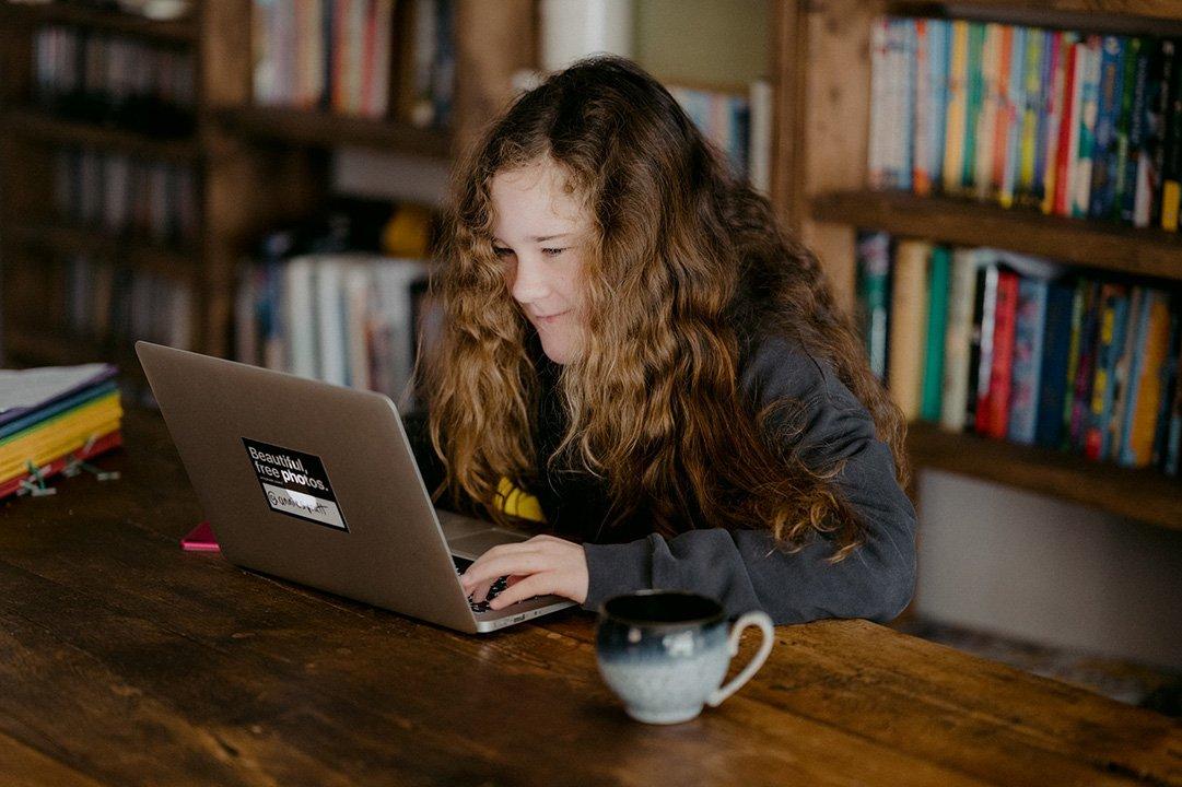 Ragazza segue una video lezione a casa utilizzando il suo computer portatile durante l'emergenza Coronavirus